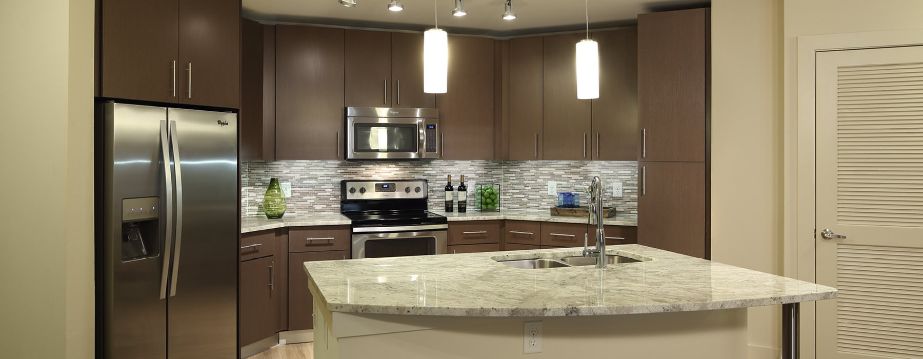 pendant lighting hangs over island in kitchen with stainless steel appliances
